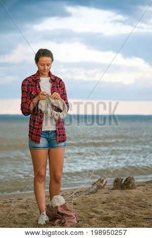 A beautiful dark-haired woman in a plaid shirt denim shorts white sneakers knits with knitting needles a gray sweater made from natural woolen thread a sweater and stands on the sand near the sea