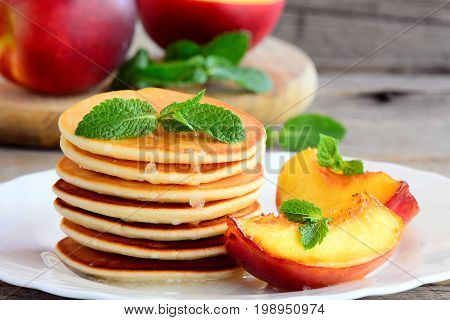 Basic pancakes with syrup and grilled fruit on a plate. Breakfast pancakes recipe for kids. Closeup