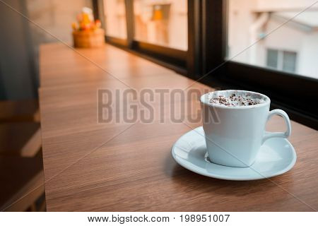 Cappuccino coffe on wood table in the morning