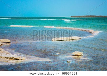 Evaporated salt along the shore of the Dead Sea. The concept of ecological and medical tourism. Israel, spring