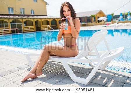 Young Woman In Swimsuit Relaxing With Cocktail On Chaise-lounge