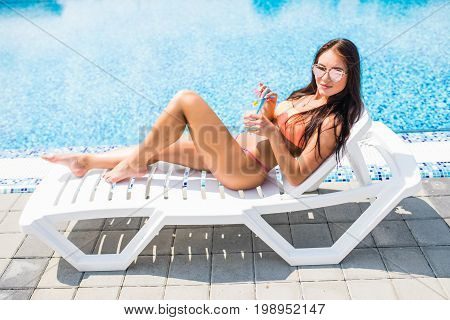Happy Young Woman With Cocktail Laying On Chaise-lounge And Looking On Copy Space