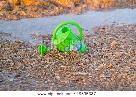 Children green toy for watering flowers on the beach.