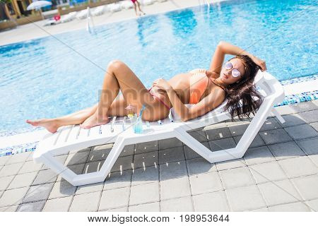 Side View Of Woman Sunbathing By The Swimming Pool And Drink Cocktail