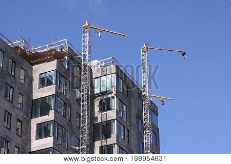 Modern urban buildings under construction with a cranes and blue sky