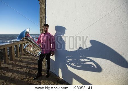 Musician with Tuba near the white wall the shadow of the tool.