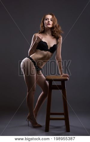 Sexy and beautiful young woman withwavy hair long legs and bronzed skin is posing in the black lacy underwear in the studio on the chair gray background