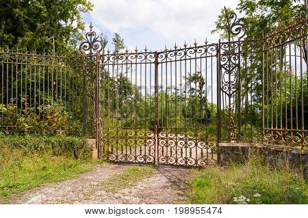 Portal of entrance of a castle with old forged gates in a forest of the Meuse in France