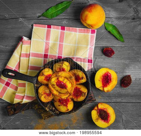 Baked peaches on a cast iron pan, leaf, cinnamon, spices for baked peaches. Fresh red fruit yellow peaches for baking, gray wooden background, board. Top view, flat lay.