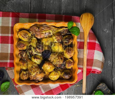 Organic Lunch Roasted chicken drumsticks and baked potatoes on ceramic tray. Ingredients for baked potatoes and chicken cheese, leaf salad, basil. Gray wooden vintage background. Top view, flat lay.
