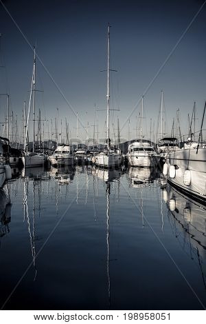 Sailboats moored in the harbour, beautiful reflection of a big long masts on the water, summer holidays on Mediterranean sea, Marmaris, Turkey