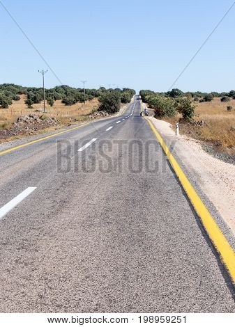 Asphalt road of local significance passing through the Golan Heights near the border with Syria in Israel