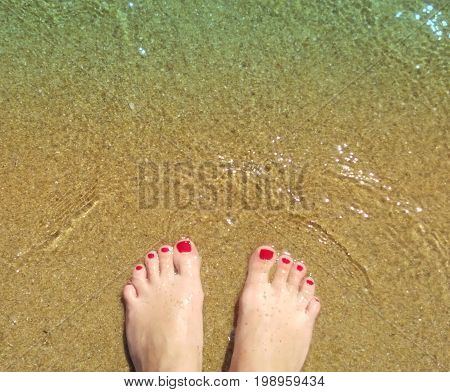 Woman's feet on the sand beach with crystal transparent waves. Symbol of vacation. Koukounaries Beach. Skiathos island Sporades archipelago. Greece
