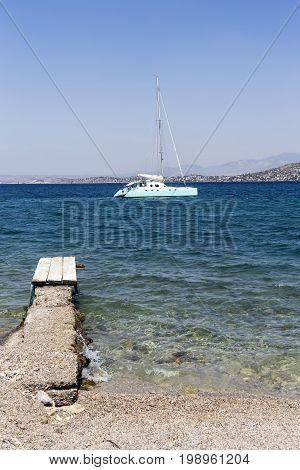 Seascape. Old, wooden pier, yacht in the distance and the blue sea