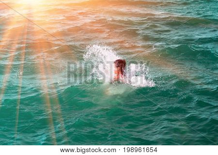 A girl disappearing in a wave jumping and immersed in a refreshing sea ocean on a hot summer day
