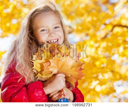 Happy girl at autumn. Little child outdoors
