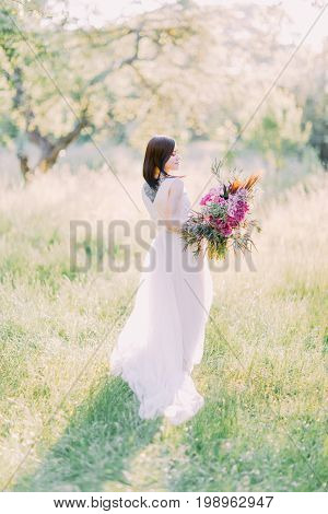 The bride with the back tattoo is the long white dress is turning around to look at the pink bouquet of the flowers. Composition of the spring field
