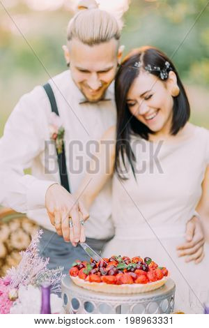 The close-up portrait of the blurred newlywed couple cutting the wedding cake with cherries and strawberries. The wedding dinner is in the sunny field