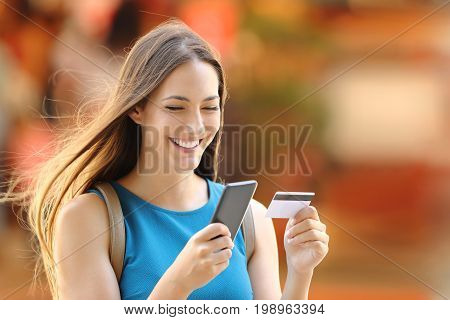 Happy shopper woman buying on line with a smart phone and a credit card on the street