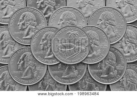 American Samoa State and coins of USA.Pile of the US quarter coins with George Washington and on the top a quarter of American Samoa State.