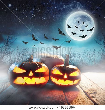 Halloween Pumpkin In A Mystic Forest At Night with moon. Elements of this image furnished by NASA