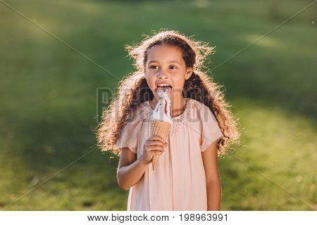 Adorable Smiling African American Girl Licking Ice Cream In Cone In Park