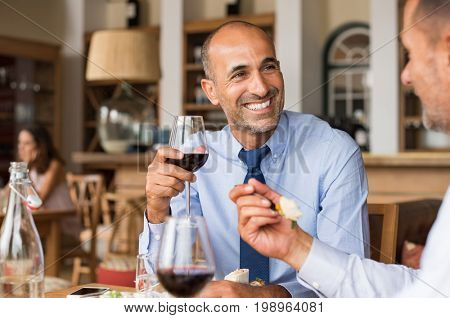 Two mature businessmen sitting in cafe and eating lunch. Two business colleagues meet in restaurant to discuss the deal. Smiling multiethnic businessman with his colleague after concluding a big deal.
