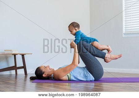 Mother with cute baby doing gymnastic exercise at home. Athletic mother holding little child on leg while doing exercise on yoga mat. Healthy mother playing and doing yoga with little boy.