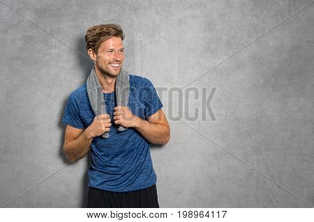 Portrait of a smiling fitness man with towel on shoulders looking away. Happy young man relaxing after training and leaning on grey wall. Sporty active guy resting after workout with copy space.