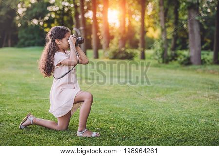 Little African American Girl Taking Photo On Professional Camera In Park With Backlit