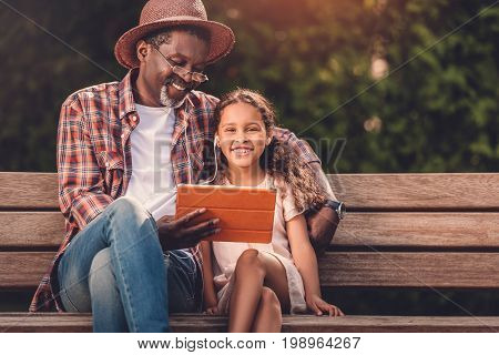 Smiling African American Grandchild And Her Grandfather Listening Music On Digital Tablet While Sitt