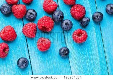 Blueberries and raspberries leaf on blue wooden table