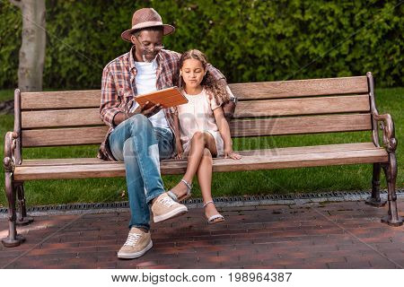 African American Grandchild And Her Grandfather Listening Music On Digital Tablet While Sitting On B