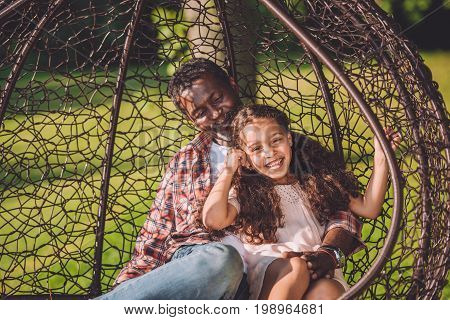 Happy African American Granddaughter And Grandfather Spending Time Together In Swinging Hanging Chai