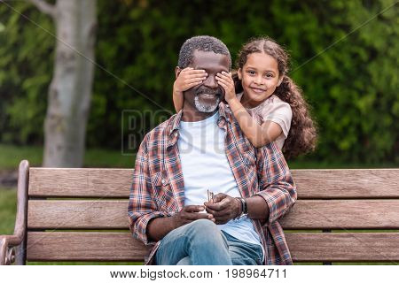 Smiling African American Girl Closing Eyes Of Her Grandfather Sitting On Bench In Park
