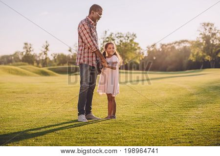 African American Granddaughter And Her Grandfather Holding Hands And Standing On Green Lawn