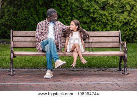 Adorable African American Girl And Her Grandfather Sitting On Bench In Park