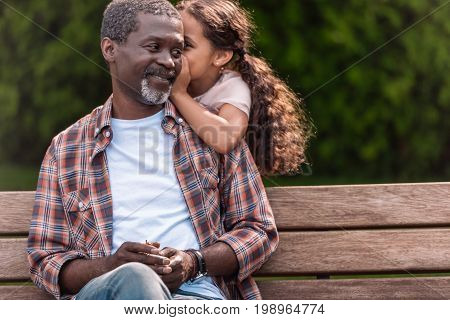 Little Adorable African American Girl Whispering To Her Grandfather While Sitting On Bench In Park
