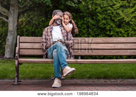 Cute African American Girl Closing Eyes Of Her Grandfather Sitting On Bench In Park