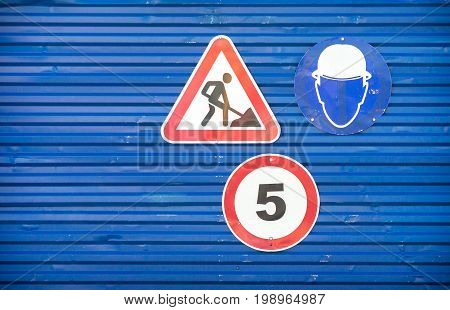 Road signs against a blue metal fence