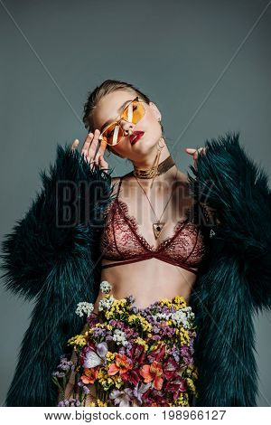 Young Sensual Beautiful Girl Posing In Orange Sunglasses, Floral Skirt, Lace Bra And Green Fur Coat