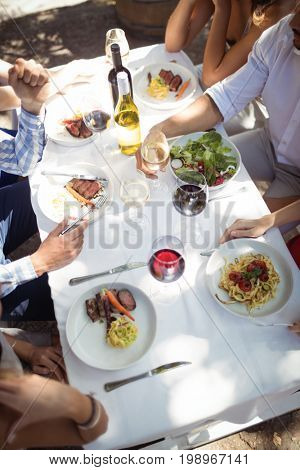 Mid-section of group of friends having lunch in a restaurant