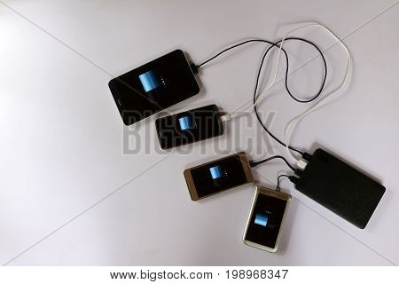power bank rechargeable batteries attached to a mobile phone in white background.