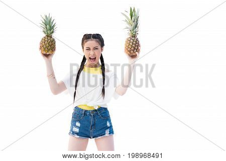 Excited Asian Girl Holding Rie Pineapples And Screaming Isolated On White