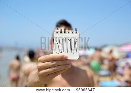 closeup of a young caucasian man in the beach showing a spiral notepad with the word summer handwritten in the first page