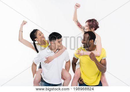 Young Multiethnic Men Piggybacking Beautiful Smiling Girls Isolated On White