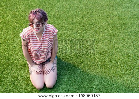 Attractive Young Woman In Sunglasses Smiling At Camera While Kneeling On Green Grass