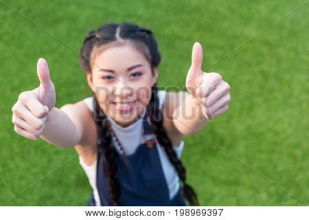 High Angle View Of Smiling Asian Girl Showing Thumbs Up While Standing On Green Lawn