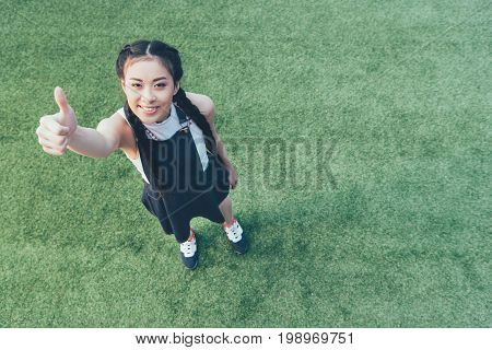 High Angle View Of Smiling Asian Girl Showing Thumb Up While Standing On Green Lawn