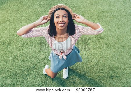 High Angle View Of Cheerful African American Girl In Straw Hat Looking Up While Standing On Grass